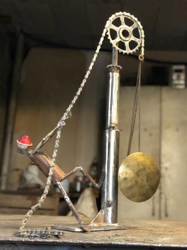 réalisé à partir d'un ancien balancier de pendule et d'un vieux phare de vélo