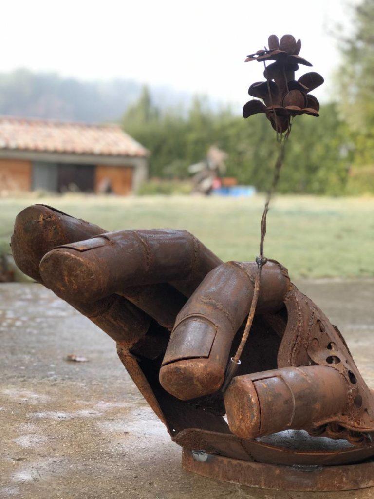 Sculpture représentant une main faite à partir d'éléments en métaux de récupération