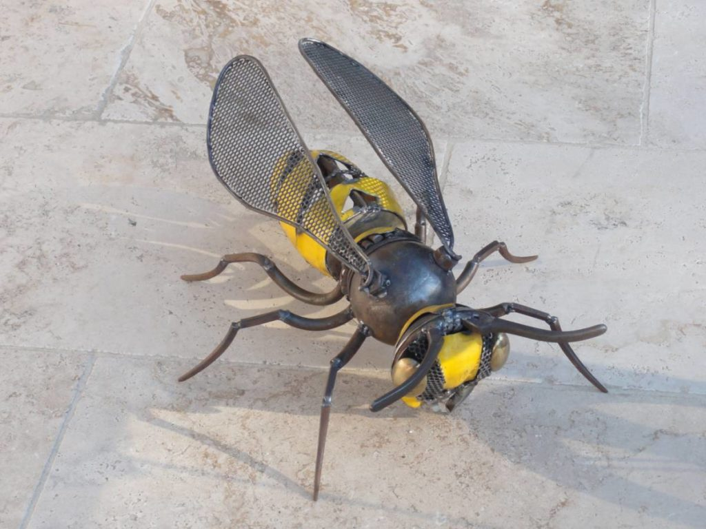 Guêpe ou abeille fabriquée à partir d'éléments de récupération en métal. Tôle jaune, morceau de chaine,.