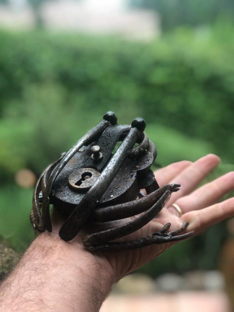 L'image représente une grenouille réalisée à partir d'un vieuc cadenas et divers éléments agricoles