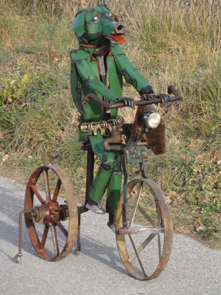 Ce chien vert a été réalisé à partir d'objets agricoles , de roues , d'un socle et de bidons en méatl vert