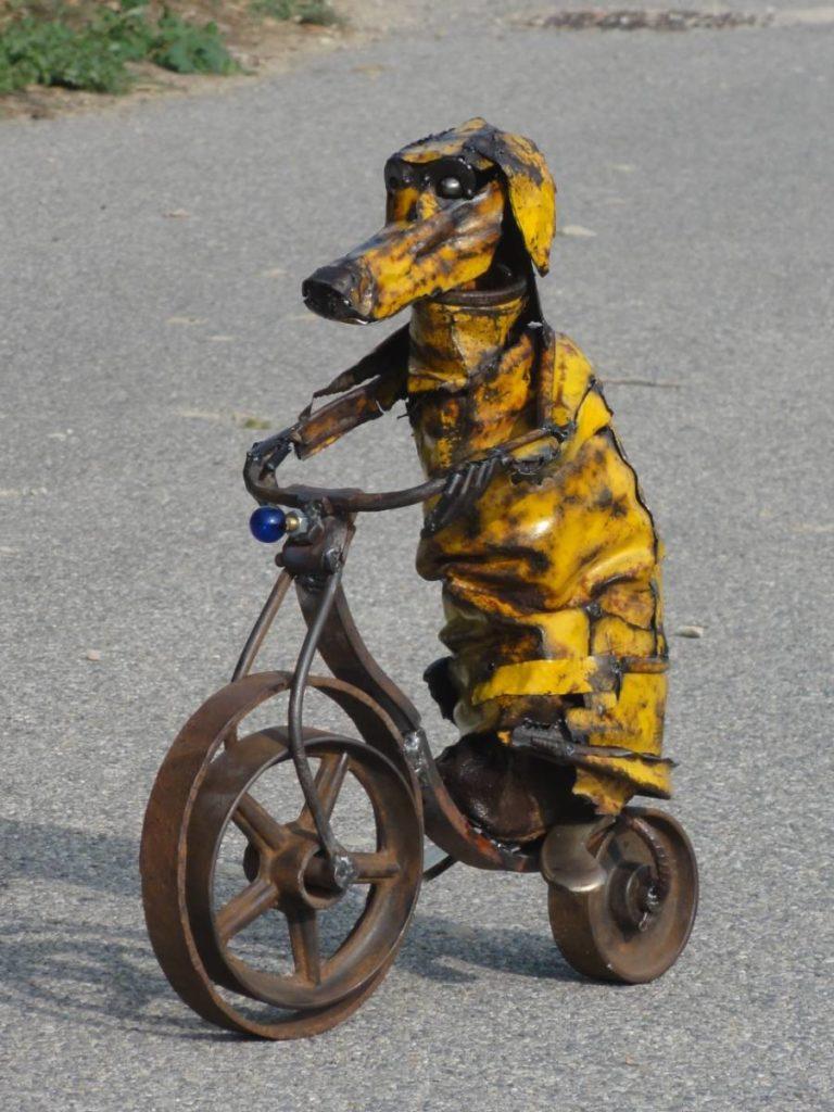 Chien jaune fait avec un vieux tonneau froissé , des roues de charrettes, une ampoule