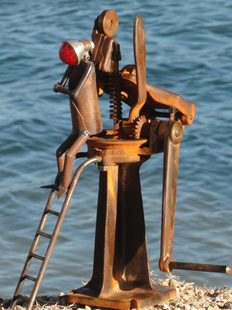 Personnage rélaisé ave un phare ancien de vélo et un appareil qui servait à faire des chaussures , utilisé par un cordonnier